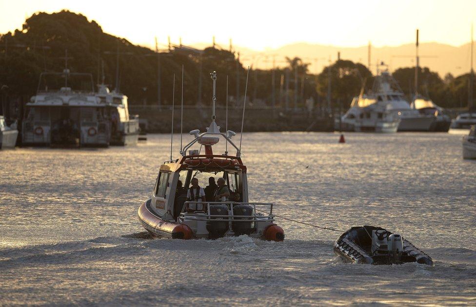 Lanchas de la Guardia Costera arrastrando un bote salvavidas.