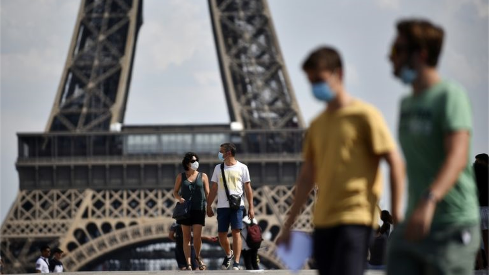 People with masks in front of the Eiffel Tower in Paris