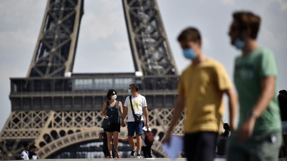 Personas con mascarilla frente a la Torre Eiffel en Paris