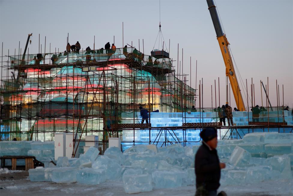 Pekerja perancah membangun struktur es di lokasi Festival Es dan Salju Internasional Harbin