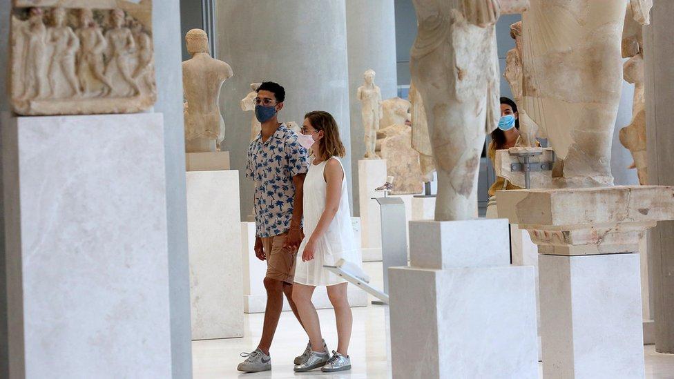 Tourists walking around the Acropolis Museum