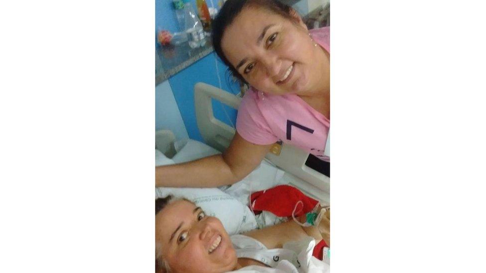Ruth e Margareth (deitada no leito de hospital) sorriem para foto
