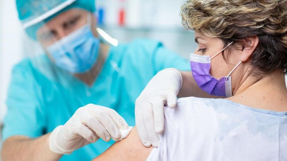 Mulher é atendida por um profissional da saúde, que segura pedaço de algodão em seu braço esquerdo