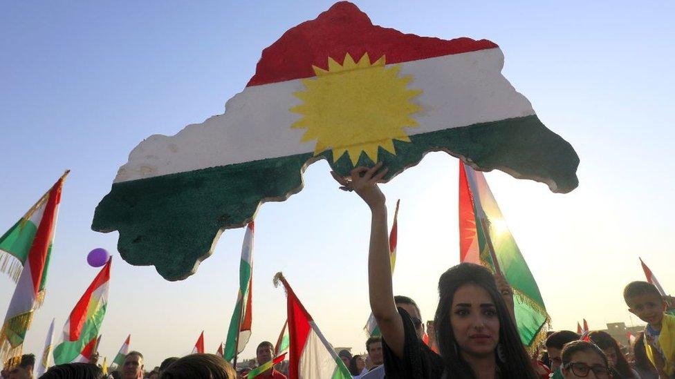 Una mujer sosteniendo un mapa con la bandera de Kurdistán.