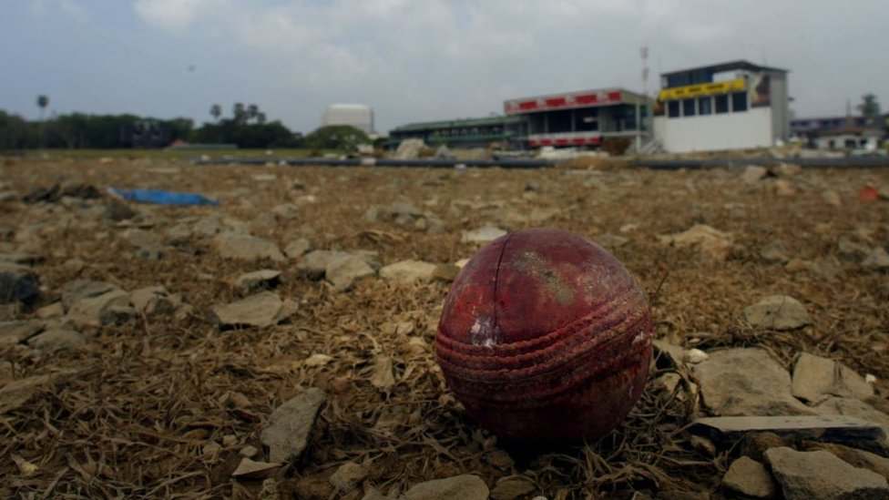 A cricket ball sits on the ground of the devastated stadium
