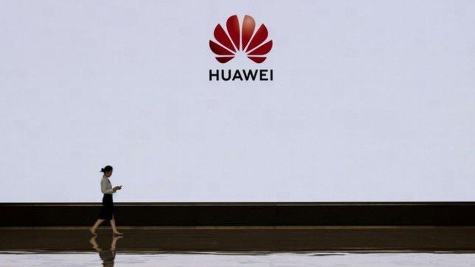 Mujer ante un logo de Huawei.
