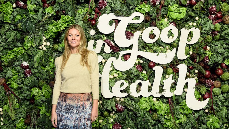 Gwyneth Paltrow stands in front of a wall of vegetables