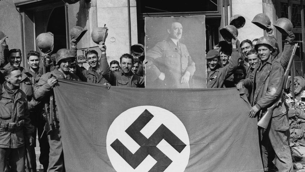 Soldados estadounidenses capturando la ciudad alemana de Saar, en 1945, con una imagen de Hitler.