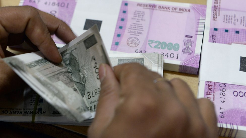 A bank staff member counts Indian 500 rupee notes to give to customers on November 24, 2016, in the wake of the demonetisation of old 500 and 1000 rupee notes in Mumbai.