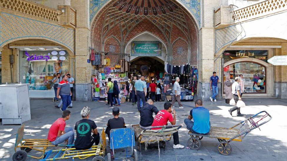 Iranians wait outside Tehran's ancient Grand Bazaar in Tehran on 28 July 2018