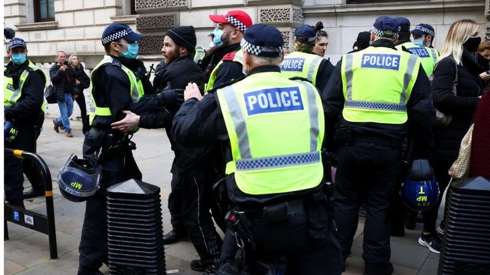 A protester being restrained by police