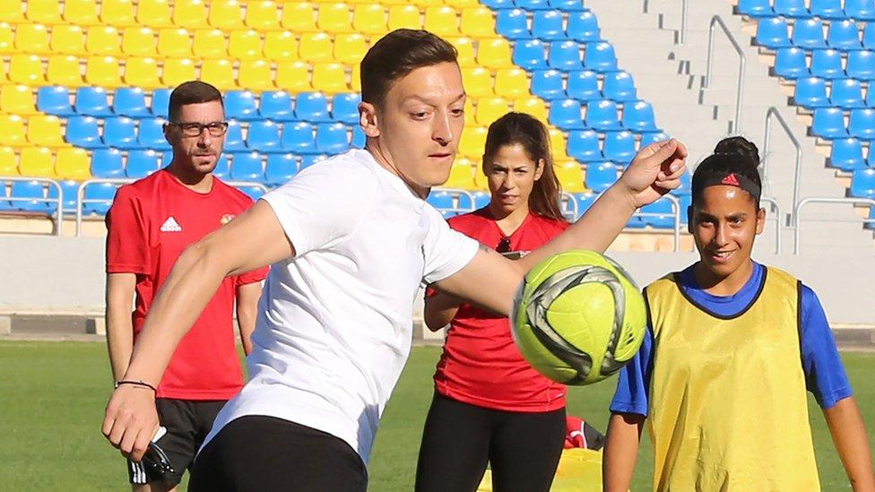 Mesut Ozil (C) plays with members of the women's U-17 Jordanian national football team