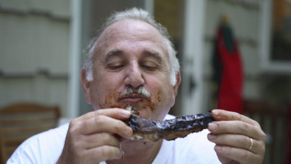 Hombre saboreando una costilla a la barbacoa