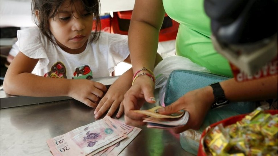 A girl looks at Venezuelan bolivar notes while her mother counts them to pay the cashier at a supermarket checkout line in Caracas on 20 October, 2015.