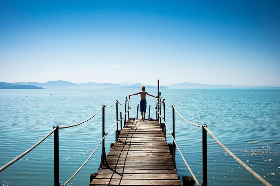 Boy on a jetty over the sea