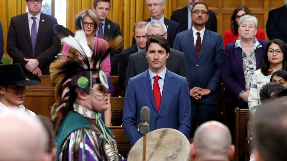 """Canada's Prime Minister Justin Trudeau listens to a drummer after delivering a statement of exoneration to the Tsilhqot""""in Nation and the descendants of six Tsilhqot""""in Chiefs in the House of Commons on Parliament Hill in Ottawa, Ontario, Canada on 26 March 2018."""