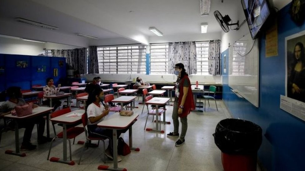 Professora com máscara e protetor facial em sala de aula com alunos sentados e com máscaras
