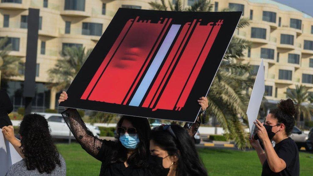 متظاهرة ترفع لافتة ضد قتل النساء في الكويت