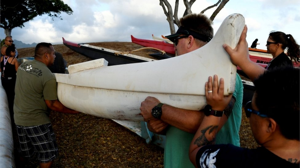 Un grupo de personas transportando canoas.