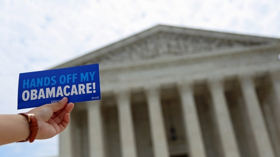 """A """"Hands off my Obamacare"""" leaflet is held up outside the US Supreme Court"""