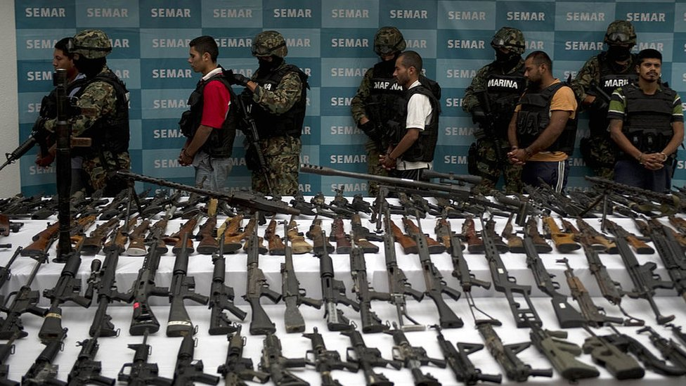 Efectivos de la Marina de México escoltan a 5 supuestos miembros del cartel de los Zetas, frente a una multitud de armas confiscadas