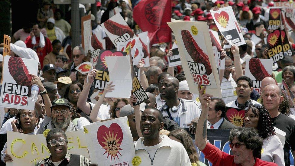 Gente marchando en EE.UU. pidiendo más acciones para acabar con el VIH.