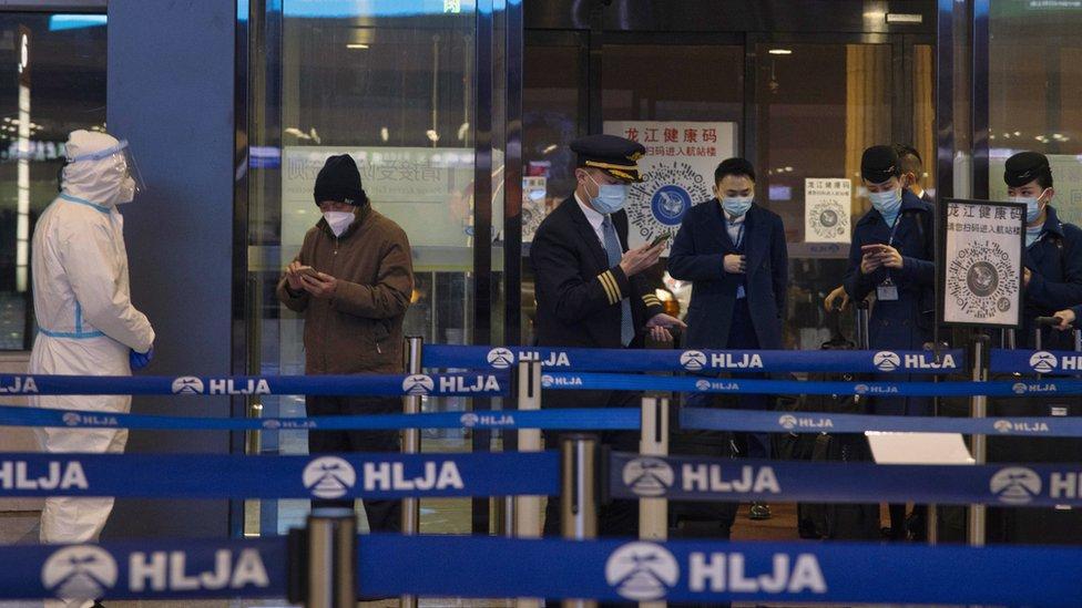 中國黑龍江哈爾濱太平國際機場進港機組人員與旅客向檢疫人員出示手機健康碼(15/1/2021)