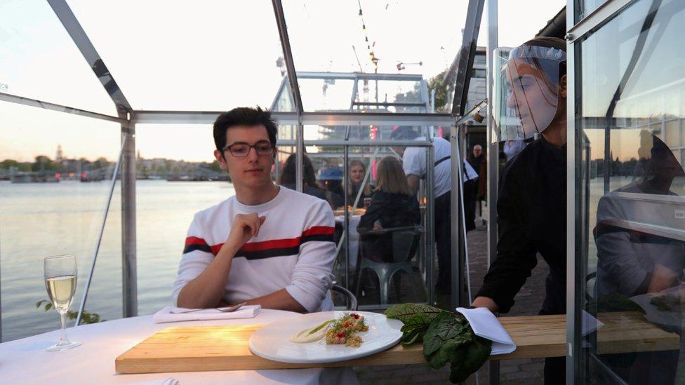 Una mesera sirve a un comensal con una tabla larga en el restaurante Mediamatic Eten, en Ámsterdam