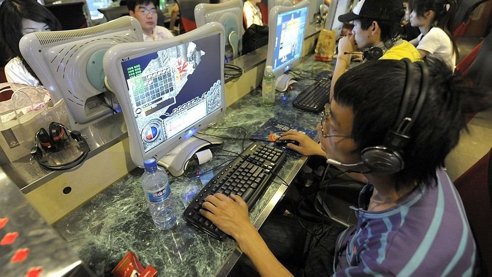 Chinese young man using a computer at a cybercafe