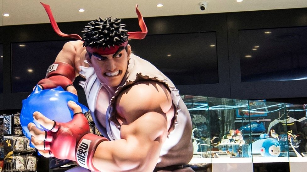 "A life-size statue of Ryu from Street Fighter, in his iconic white karate suit and red bandana, prepares a ""hadouken"" energy ball. In the background is a Capcom brand store"