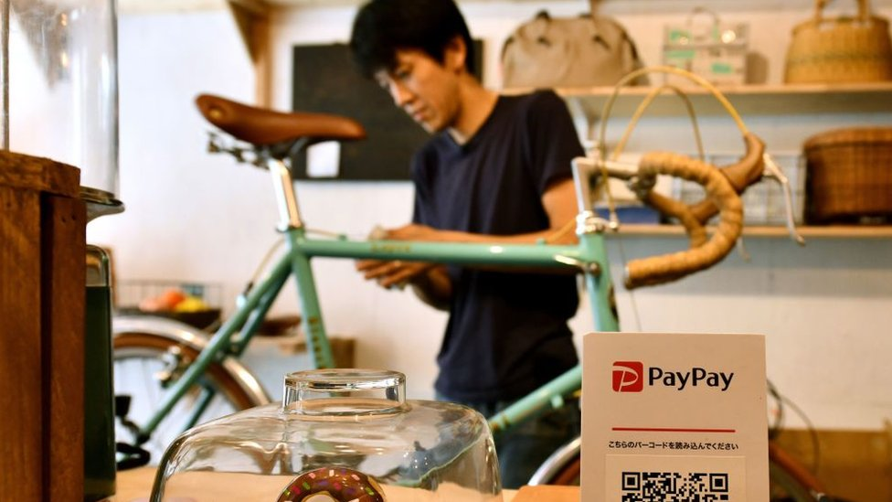 PayPay logo in front of a man repairing a bicycle.