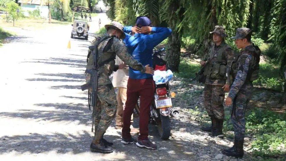 Soldados revisan a un vecino de El Estor.