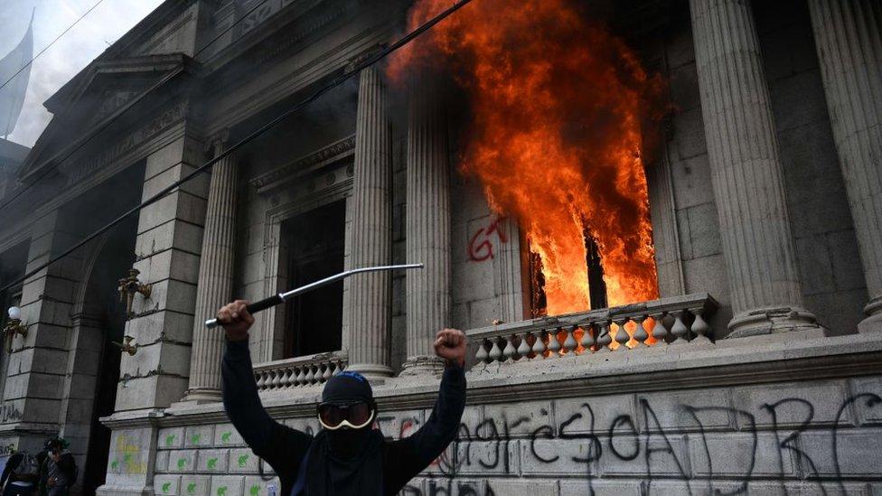 Un manifestante encapuchado frente a las oficinas del Congreso incendiadas.