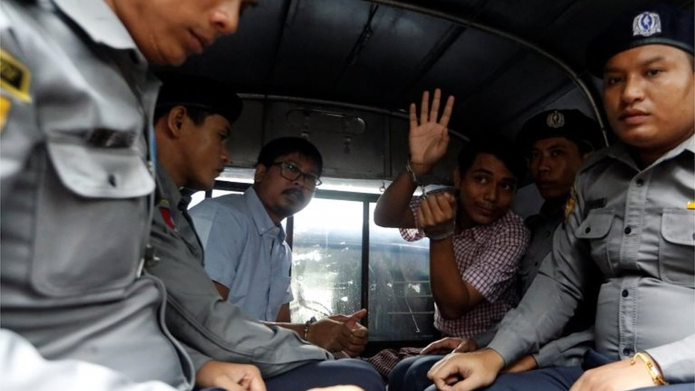 Detained Reuters journalist Wa Lone and Kyaw Soe Oo sit beside police officers as they leave Insein court in Yangon, Myanmar July 9, 2018.