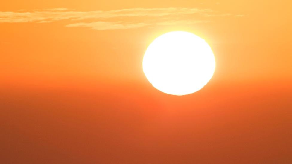 قرص الشمس ساطع وقد اكتست السماء باللونين الأحمر والبرتقالي