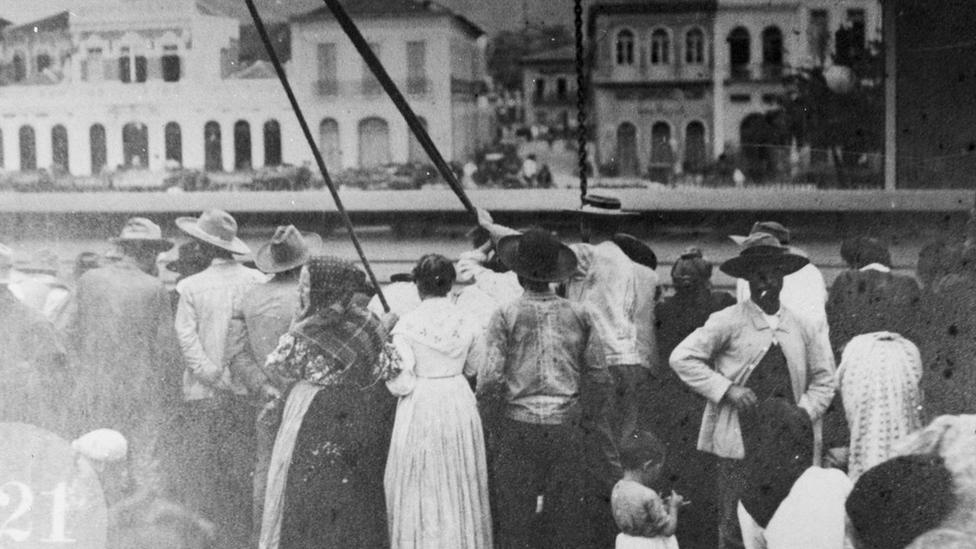 Foto em preto e branco mostra dezenas de homens e mulheres no porto