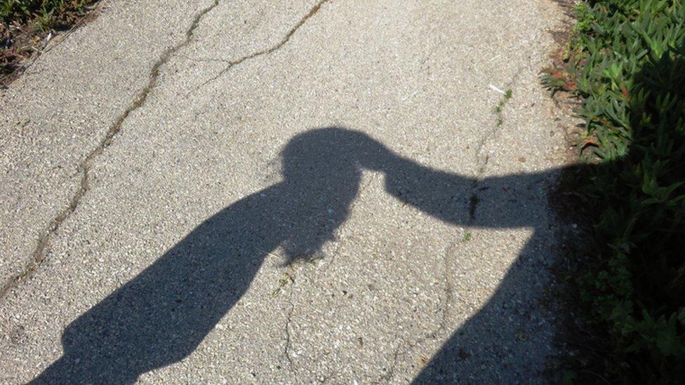Sombra de un adulto tocando en la cabeza a una niña.