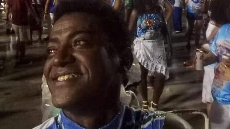 Homem sorrindo com arquibancada ao fundo