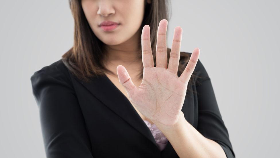 Mujer con la mano alzada en señal de rechazo.