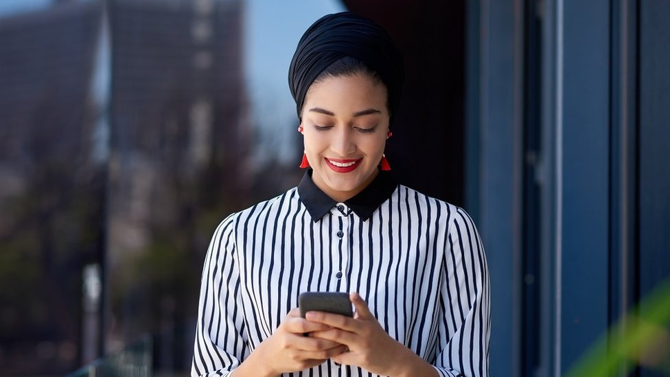A young businesswoman using a smartphone on the balcony of a modern office building