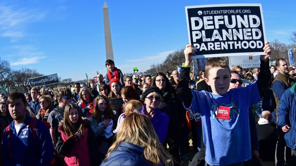 Kid holds 'defund planned parenthood' sign