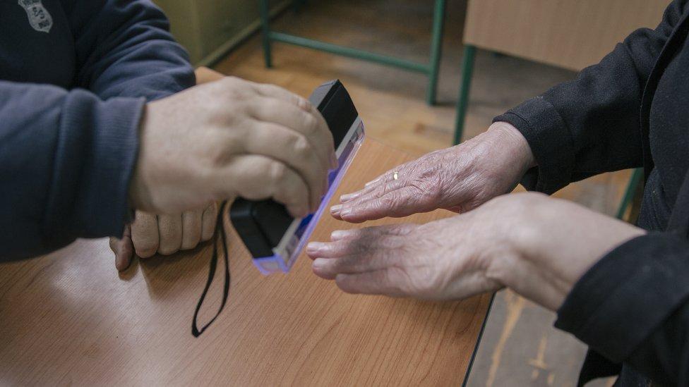 Članovi biračog odbora UV lampom proveravaju da li je neko već glasao