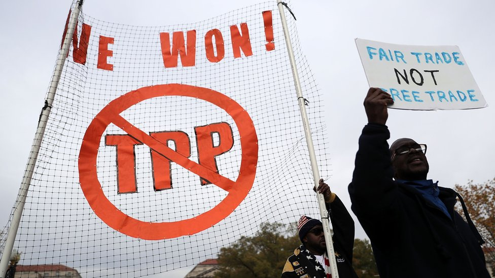 """Activists shout slogans as they march during an anti-Trump and anti-TPP protest November 14, 2016 in Washington, DC. Activists held a rally and a march """"to protest the Trans-Pacific Partnership and urge President-elect Donald Trump and members of Congress to reject the trade deal."""