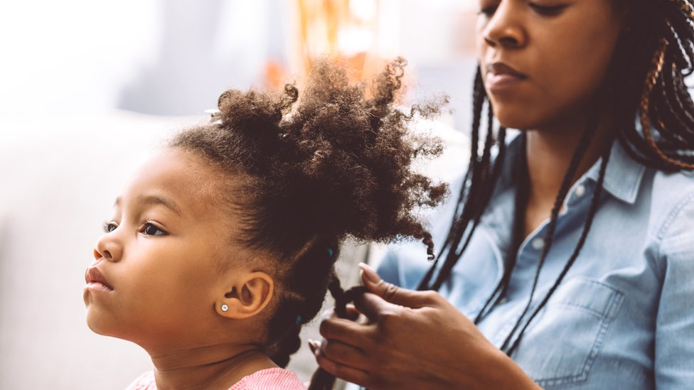 A mother plaiting her daughter's hair - generic