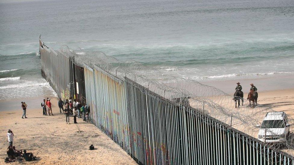 Migrantes junto a la valla fronteriza en Playas de Tijuana