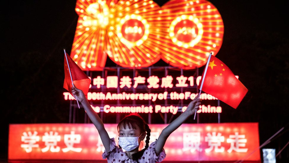 A girl wearing a mask whilst waving the national flag during the centenary of the founding of the CPC history lantern show at Expo Garden on June 25, 2021 in Wuhan, Hubei. China.