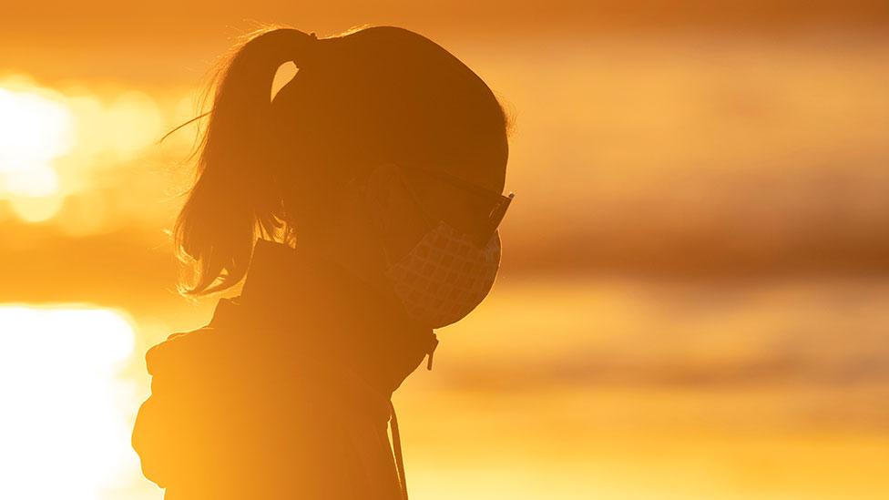California beach sunset, wearing a mask