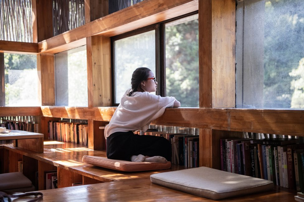 A woman looking out of a window in Liyuan Library
