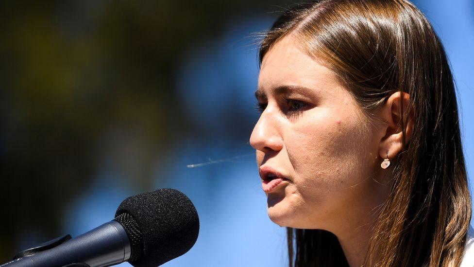 امرأة تتحدث أمام ميكروفون