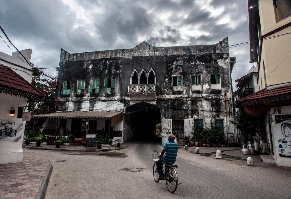 A man cycles in Zanzibar